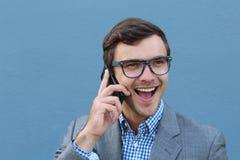 年轻人使人惊奇谈话在他的在蓝色背景的手机 库存图片