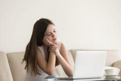 年轻人使在家感觉昏昏欲睡坐与膝上型计算机的妇女不耐烦 免版税库存图片