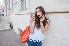年轻人使拿着唇膏和看她的电话的妇女惊奇 免版税库存图片