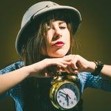 年轻人使拿着闹钟的遮阳帽的妇女惊奇 免版税库存照片