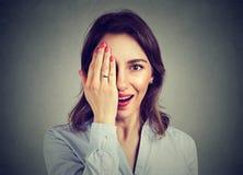 年轻人使掩藏半面孔用她的手的妇女惊奇 库存图片