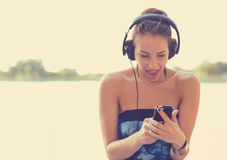 年轻人使有耳机的妇女惊奇听到在巧妙的电话的音乐的 免版税库存图片