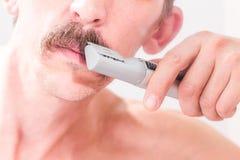 人使用一个整理者整理他的髭 特写镜头 免版税库存照片