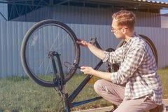 人使用一个气汞 骑自行车者修理在旅行的自行车 库存图片