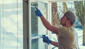 年轻人使用一块旧布和橡皮刮板,当清洗窗口时 免版税库存图片