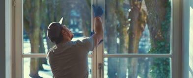 年轻人使用一块旧布和橡皮刮板,当清洗窗口时 库存照片