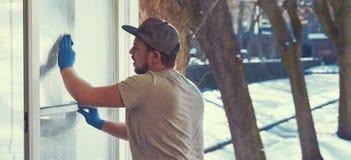 年轻人使用一块旧布和橡皮刮板,当清洗窗口时 库存图片