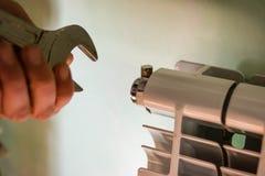 人使用一把板钳改变幅射器打破的通风孔 免版税库存照片