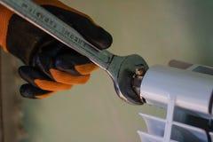 人使用一把板钳改变幅射器打破的通风孔 免版税库存图片