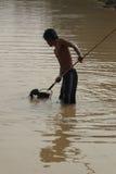 年轻人使用一把犁耙抓鱼 图库摄影
