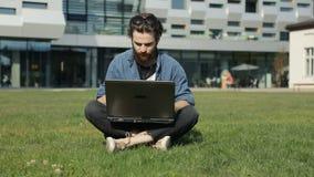 人使用在草的膝上型计算机 影视素材