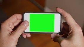 人使用空白的绿色屏幕智能手机打比赛 股票录像