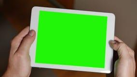 人使用空白的绿色屏幕片剂个人计算机打比赛 股票视频