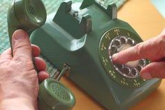 人使用老转台式电话 库存图片
