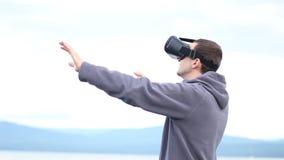 人使用虚拟现实玻璃反对天空和风景 股票录像