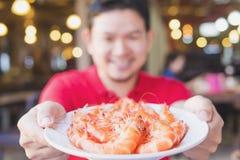 人供食在一块白色板材的蒸的虾 库存图片