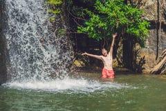 年轻人侧视图有站立反对瀑布的胳膊的 库存图片