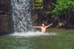 年轻人侧视图有站立反对瀑布的胳膊的 免版税库存照片