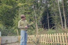 年轻人修剪一棵树在庭院里 免版税库存图片
