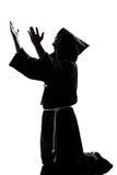 人修士祈祷的教士剪影 免版税图库摄影