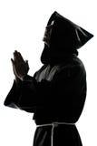 人修士祈祷的教士剪影 免版税库存图片
