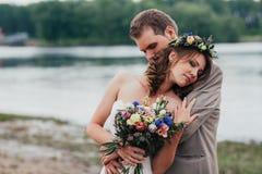年轻人修饰和站立的新娘拥抱在河的背景 图库摄影