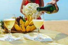 人倒香槟入在一块板材的背景的一块玻璃用果子 在海滩的庆祝 库存图片