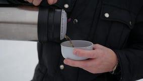 人倒从热水瓶的热的茶户外 花雪时间冬天 股票视频