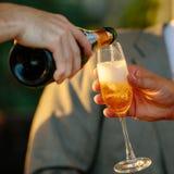 人倒从瓶的香槟在杯另一个人 海岸夜间芬兰海湾光彼得斯堡st 手射击,方形的图象 库存照片
