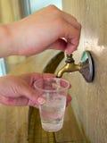人倾倒在矿物春天之上的水在塑料杯子 免版税库存图片