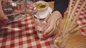人倾吐从蒸馏瓶的干净的饮用水入玻璃 关闭 股票视频