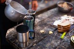 人倾吐煮沸的水到在木桌上的热的杯子在早餐期间在森林阵营 野餐的人野营在的 免版税库存图片