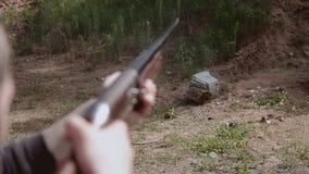 人做一把猎枪被射击在老显示器 在击中对地面的显示器秋天以后 肩膀的特写镜头 股票录像