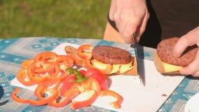 人做三明治用炸肉排、乳酪、面包和胡椒 递特写镜头 股票录像
