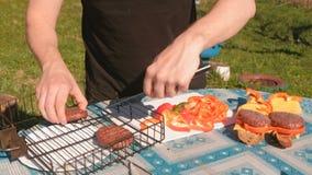人做三明治 采取从格栅的炸肉排并且投入面包用乳酪和胡椒 递特写镜头 股票录像