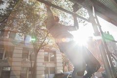 年轻人做在脚手架的引体向上在NYC 库存照片