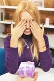 年轻人做礼物给闭上她的眼睛的女孩 免版税图库摄影