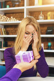 年轻人做礼物给闭上她的眼睛的女孩 免版税库存照片