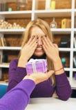 年轻人做礼物给闭上她的眼睛的女孩 图库摄影