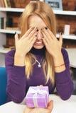 年轻人做礼物给闭上她的眼睛的女孩 免版税库存图片
