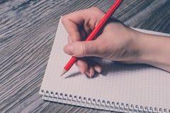 人做笔记的` s手照片的旁边外形关闭对笔记本使用红色笔铅笔 Felame与pencile的手文字 免版税库存图片