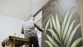 人做艺术壁画 街道画与油漆的艺术家图画在墙壁上 艺术背景黑色概念屏蔽油漆红色地点白色 影视素材