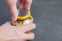 人关上一个瓶子的盒盖在蜂蜜的坚果 递特写镜头 免版税库存照片