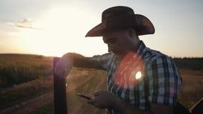 人农夫戴帽子在日落和在smarphone工作 与顾客的通信 现代的商业 股票录像