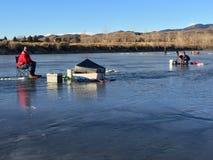 人冰在蓝色冰的渔在蓝天3下 免版税库存图片