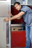 年轻人冰箱的开门画象  图库摄影