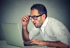 年轻人冲击了使用便携式计算机的人坐在桌 库存照片