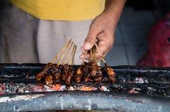 人准备在巴厘岛,印度尼西亚心满意足在地方街市上的ayam 库存照片