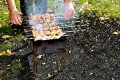 人准备在火的肉 免版税库存照片