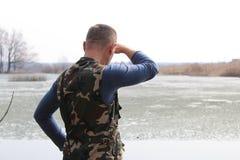 人凝视入距离,当站立在湖的岸时 免版税库存照片